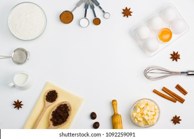 Cooking baking flat lay background with eggs, yolk, a cup of butter, a cup of flour, milk, spices cinnamon, anise and kitchen tools sieve whisk rolling pin measuring spoons. Place for copy space.