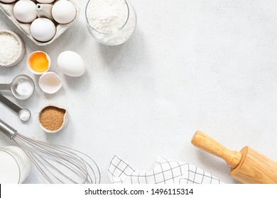 Cooking And Baking Ingredients Utensils On White Concrete Background. Kitchen Food Frame. Eggs Sugar Milk Whisker Rolling Pin And Measuring Spoons With Spices