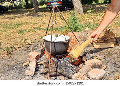 Cooking barbecue and fish soup on a bonfire on a picnic outside the city. Summer, 2019.