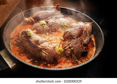 cooking beef roulades, german stuffed meat rolls with vegetables and sauce steaming in a pan on the black stove, selected focus, narrow depth of field