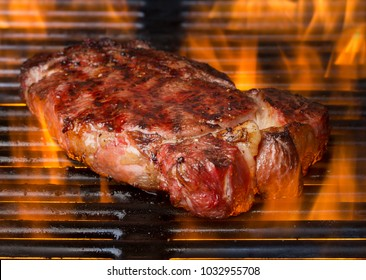 cooking beef steak on grill grates with big spurts of flame