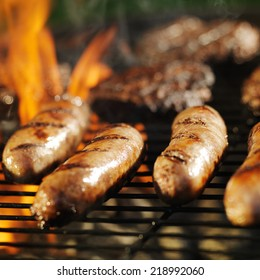 cooking bratwursts over flaming grill