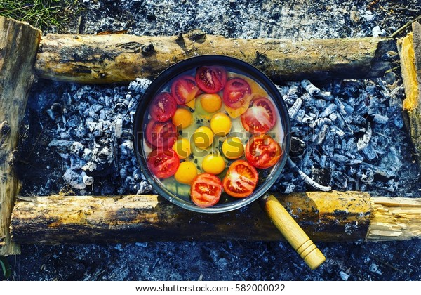 Cooking breakfast on a fire in a tent camp.