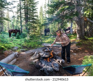 Cooking breakfast over a campfire in the Rockies with horses in the background