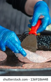 Cooking burgers and raw meat on a griddle wearing blue gloves to meet food hygiene standards