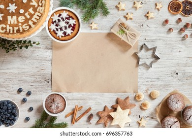 Cooking butter biscuits on a wooden table with Christmass accessories such as snowflakes, sweets, cinnamon, on a beige wooden background. Christmass background with branches of furry spruce. Top view.
