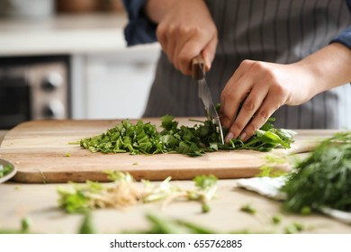 Cooking. Chef is cutting greens in the kitchen