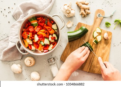 Cooking - chef's hands preparing vegetable vegetarian stew (thick soup). Kitchen scenery - pot with recipe ingredients around on the grey stone worktop captured from above (top view, flat lay).