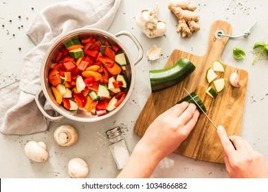 Kochen - Koch-Hände bereiten vegetarischen Eintopf (dicke Suppe). Küchenlandschaft - Topftopf mit Zutaten aus Rezepten auf dem grauen Stein, der von oben aufgenommen wurde (Draufsicht, flacher Laibe).