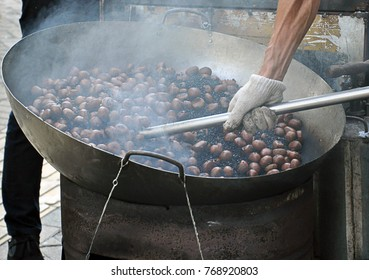 A cooking of chestnut. Chestnuts are being roasted in big chinese brass pan or wok on a stove with hot black stone for heating up ready for sell.