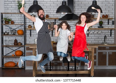 Cooking with child might be fun. Having fun in kitchen. Family mom dad and little daughter wear aprons jump in kitchen. Family having fun cooking together. Teach kid cooking food. Weekend breakfast.