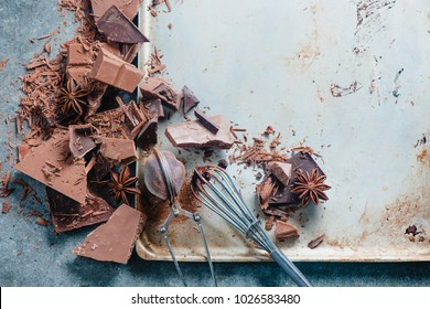 Cooking chocolate at home. Dessert ingredients, cocoa powder, cinnamon and anise stars on a marble kitchen table with a whisk for glazing and a cocoa strainer.