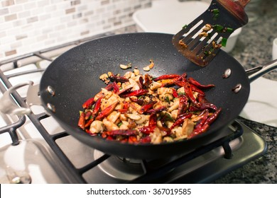 cooking chongqing chicken in wok at home, traditional szechuan (sichuan) chinese meal