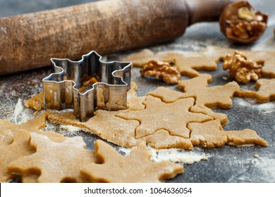 Cooking Christmas cookies with  cookie cutters on a dark table