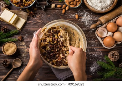 Cooking christmas fruit cake.  young woman's hands mixing ingredients in bowl. Wooden table. Top view