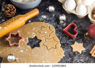 Cooking Christmas gingerbread cookies with ingredients on a dark background.