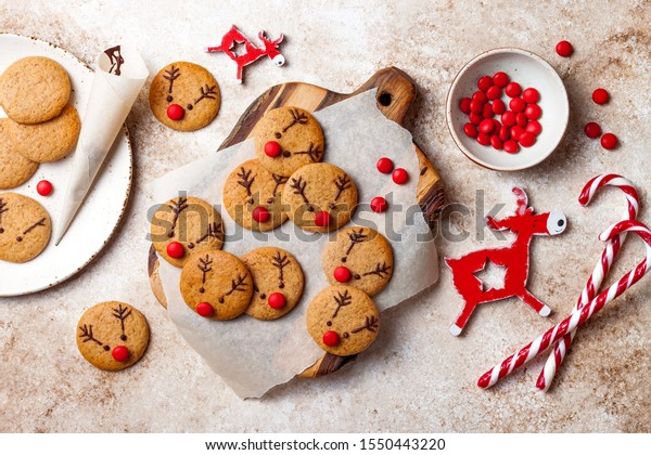 Cooking Christmas gingerbread. Decorating red nosed reindeer cookies with chocolate buttons and melted chocolate. Festive homemade decorated sweets