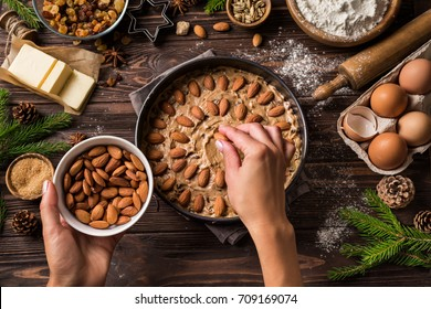 Cooking christmas pastry. Young woman's hands decorating festive fruit cake with almond. Wooden table with baking ingredients. Top view.