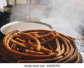 Cooking of churros. ring of churros and cut churros sticks. Huge ring of Churros boiling in oil, steam coming up on a background. Spanish (Mexican) cuisine.  Inside old churreria. Horizontal photo