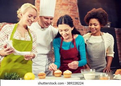 cooking class, culinary, bakery, food and people concept - happy group of women and male chef cook baking in kitchen