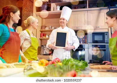cooking class, culinary, food and people concept - happy women and chef cook with blank menu chalk board in kitchen