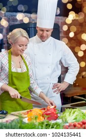 cooking class, culinary, food and people concept - happy male chef cook with woman cooking in kitchen