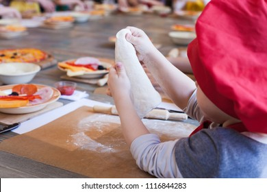 cooking class, culinary. Food and people concept, desktop getting ready for work, ingredients for italian pizza. Kid hands in work progress