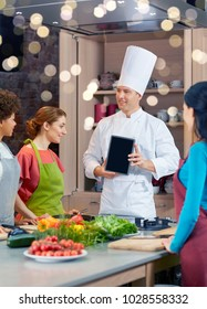 cooking class, culinary, food, technology and people concept - happy women with chef cook showing blank tablet pc screen in kitchen
