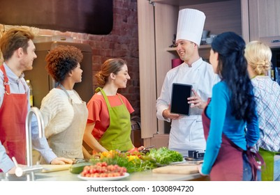 cooking class, culinary, food, technology and people concept - happy friends with chef cook showing blank tablet pc screen in kitchen