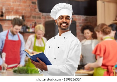 cooking class, profession and people concept - happy male indian chef in toque reading cookbook over group of students background
