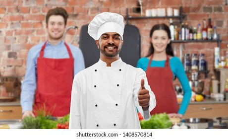 cooking class, profession and people concept - happy male indian chef in toque showing thumbs up over students background