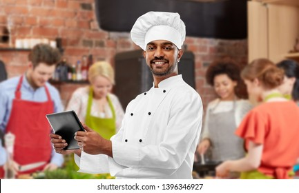 cooking class, technology and people concept - happy male indian chef in toque with tablet computer over group of students background