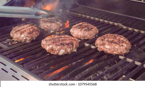 Cooking classic beef burger on outdoor gas grill.