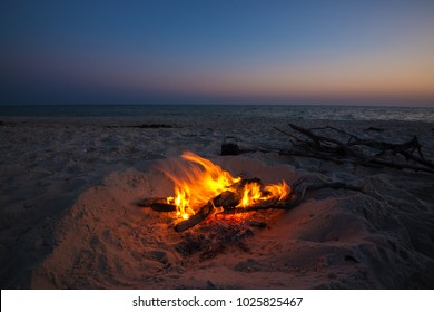 Cooking coffee while traveling on the wild seashore -  small kettle stands next to a blazing bonfire  on the background of colorful sky over the sea after sunset.
