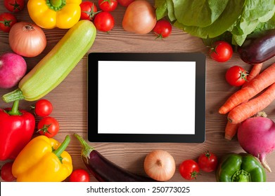 Cooking concept. Digital Recipe book. Tablet pc and ingredients for cooking vegetables over wooden background. Top view