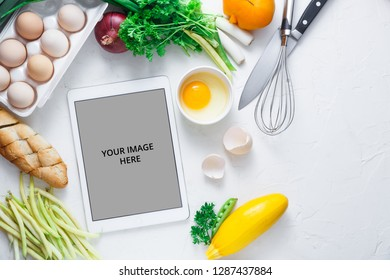 Cooking concept, tablet computer and breakfast ingredient on white bacjground