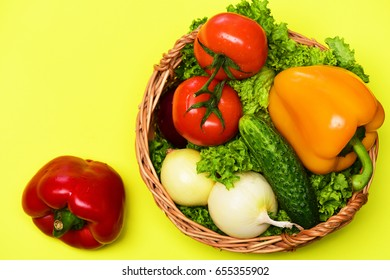 cooking concept, vegetables or lettuce leaf, tomatoes with onions, peppers, cucumber in basket isolated on yellow background