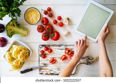 Cooking, culinary, food, technology and people concept. Young woman using a tablet computer to cook in her kitchen. A woman searching the cooking menu and preparing food ingredient before cooking.