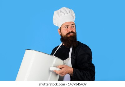 Cooking, culinary. Male chef cook holds big pot. Food, profession and people concept. Cook man in apron holds saucepan in kitchen. Cooking pot, saucepan, casserole. Cookware, dinnerware, kitchenware.
