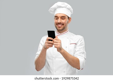 cooking, culinary and people concept - happy smiling male chef in toque with smartphone over grey background