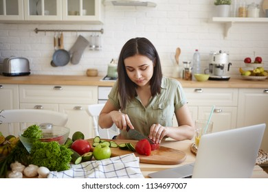 Cooking, culinary, quinine, food and nutrition concept. Indoor shot of hardworking young housewife with dark hair slicing red bell pepper and cucumber while making vegetable meal for dinner