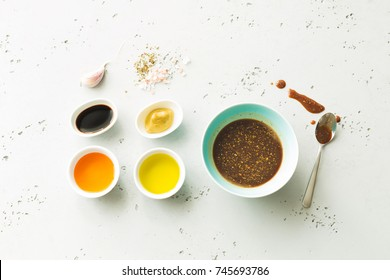 Cooking - dark brown salad dressing and recipe ingredients (balsamic vinegar, honey, olive oil, mustard, garlic, salt). Layout captured from above (top view, flat lay). Grey stone background.