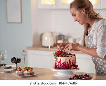 cooking and decoration of cake with cream. Young woman pastry chef in the kitchen decorating red velvet cake with flowers and berries. Master pastry chef completes work on a birthday cake
