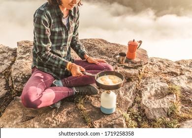 Cocina de un delicioso y saludable desayuno con huevos y café en una quemadora de gas mientras acampa en las montañas
