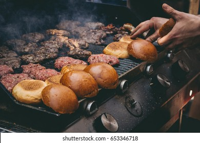 Cooking delicious juicy meat burgers and buns on the grill outdoor. Selective focus