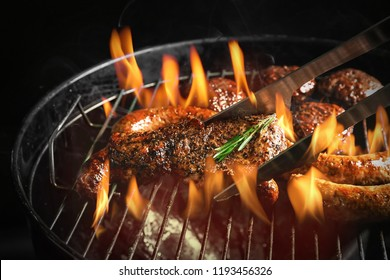 Cooking of delicious steak with sausages on barbecue grill