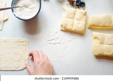 Cooking delicious sweets with jam and cinnamon and powder to tea.Top view. Female hands prepare a cake on a table where there are several pieces of dough and a plate of cream. Sunny day. Flat lay.
