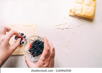 Cooking delicious sweets with jam and cinnamon and powder to tea.Top view. Womans hands are preparing a cake by laying berries on the dough. On a white table lies a dough. Sunny morning.Flat lay.