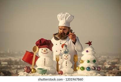 Cooking and diet concept. Cook, snowmen and snow xmas tree on blue sky. Hipster with ladle in white uniform. Man in chef hat ladling soup on winter day. Christmas and new year holidays food.