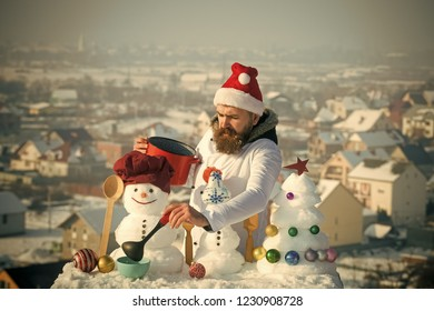 Cooking and diet concept. Man in santa hat ladling soup on winter day. Cook, snowmen and snow xmas tree on blue sky. Hipster with ladle in white uniform. Christmas and new year holidays food.